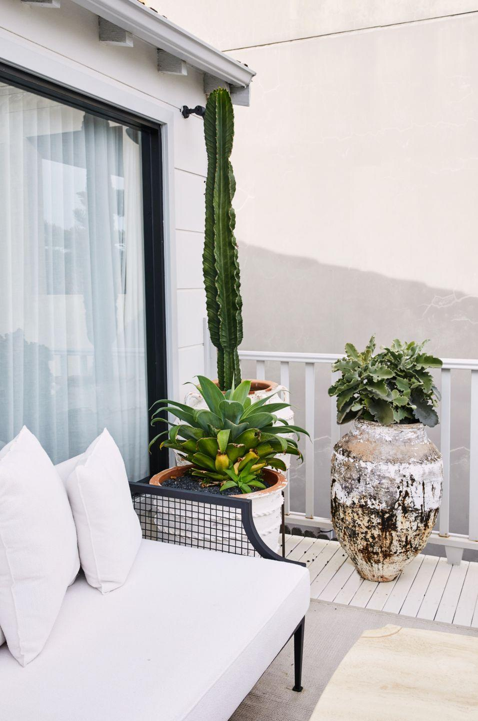 "<p>Add greenery with<a href=""https://www.housebeautiful.com/lifestyle/gardening/g31355906/easy-low-maintenance-plants/"" rel=""nofollow noopener"" target=""_blank"" data-ylk=""slk:low-maintenance plants,"" class=""link rapid-noclick-resp""> low-maintenance plants,</a> like cacti. Though this deck is small, interior designer Tamsin Johnson still added plenty of personality and color with rustic planters and tall plants that take advantage of the vertical space. </p>"