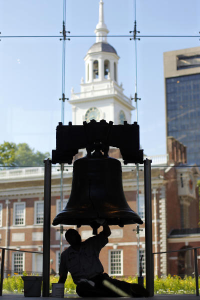 FILE - In this June 7, 2012 file photo, technician Jonathan Miller buffs the interior surface of the Liberty Bell as part of regular conservation work, in view of Independence Hall, at Independence National Historical Park, in Philadelphia. The City of Brotherly Love is perhaps best known for its Colonial roots but locals will tell you there's much more to explore in this city of 1.5 million people. (AP Photo/Matt Rourke, File)