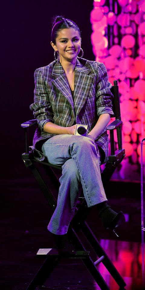 <p>Selena Gomez wore a plaid blazer with a bandeau top, blue jeans, silver hoop earrings, and black heels while promoting her new album.</p>