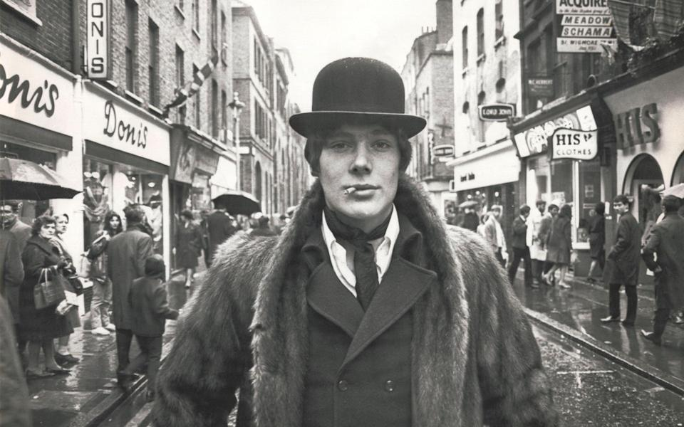 UNITED KINGDOM : Fashionable male wearing a bowler hat and fur coat standing in the middle of the road on Carnaby Street in London in the heart of the ?Swinging Sixties?. (Photo by SSPL/Getty Images)  - Getty