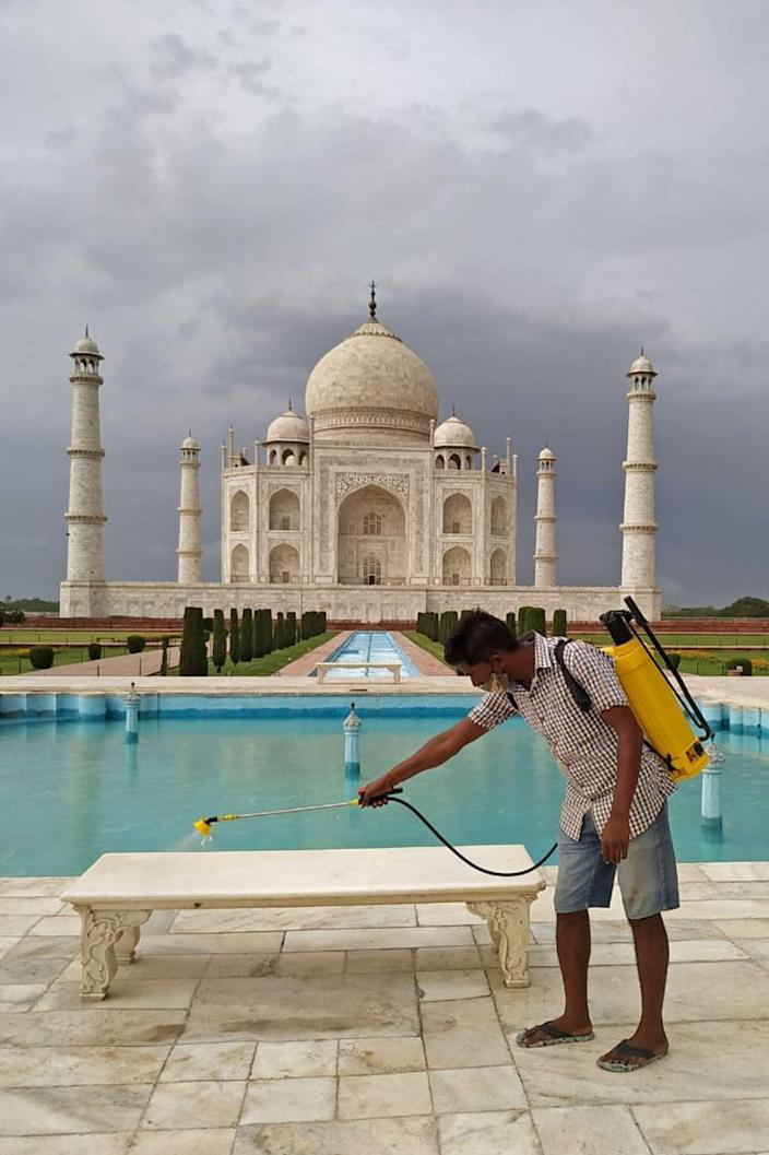 A sanitation worker sprays disinfectant on the marble bench at the premises of Taj Mahal mausoleum on the eve of its reopening to public after two months due to the lockdown (AFP via Getty Images)