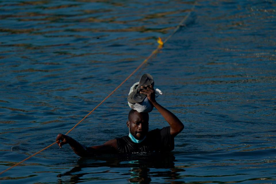 A Haitian migrant wades across the Rio Grande from Del Rio, Texas, to return to Ciudad Acuña, Mexico, Tuesday, Sept. 21, 2021, to avoid deportation from the U.S.