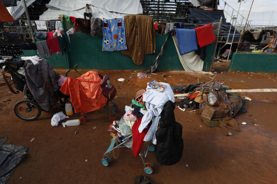 Belongings are stacked on strollers while mattresses and blankets hang on lines to dry, a day after heavy rains, inside the Benito Juarez sports complex in Tijuana, Mexico, Friday, Nov. 30, 2018. Authorities in the Mexican city of Tijuana have begun moving some of more than 6,000 Central American migrants from an overcrowded shelter on the border to an events hall further away.(AP Photo/Rebecca Blackwell)