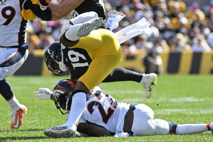 Pittsburgh Steelers wide receiver JuJu Smith-Schuster (19) is upended by Denver Broncos safety Kareem Jackson (22) during the first half of an NFL football game in Pittsburgh, Sunday, Oct. 10, 2021. Smith-Shuster was injured on the play and left the field. (AP Photo/Don Wright)