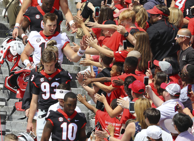 Georgia quarterback Jake Fromm high fives fans entering Sanford Stadium in the Dawg Walk for Georgia's annual G-Day spring intrasquad football game on Saturday, April 21, 2018, in Athens, Ga. (Curtis Compton/Atlanta Journal-Constitution via AP)