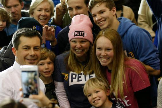 Pete Buttigieg poses for selfies with supporters while campaigning at Dover Middle School in New Hampshire (EPA)