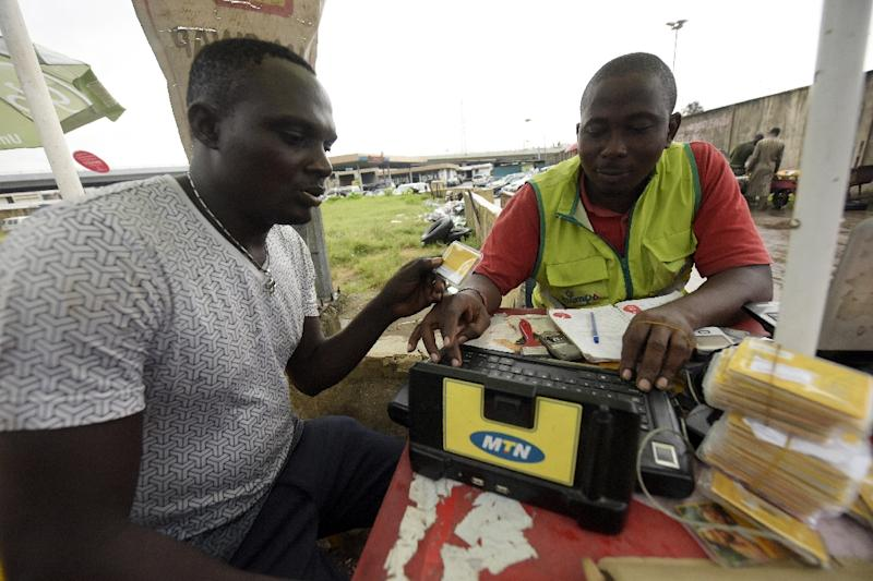 A MTN service provider tries to register a client's SIM card in Lagos, in October 2015 (AFP Photo/Pius Utomi Ekpei)