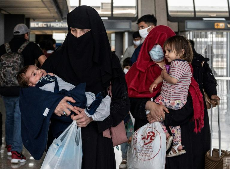 Refugees from Afghanistan are escorted to a waiting bus after arriving at Dulles International Airport in Dulles, Virginia