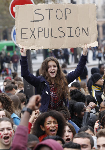High school students, one holding a poster, demonstrate against the police expulsions of immigrant families — including some of their classmates, Friday, Oct. 18, 2013 in Paris. Anger erupted this week over the treatment of a 15-year-old Kosovar girl who was detained in front of classmates on a field trip. The government says her eight-member family had been denied asylum and was no longer allowed to stay in France. (AP Photo/Christophe Ena)
