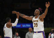 Los Angeles Lakers forward Carmelo Anthony (7) gives a high five to Los Angeles Lakers center Dwight Howard (39) in the first half of a preseason NBA basketball game against the Phoenix Suns in Los Angeles, Sunday, Oct. 10, 2021. (AP Photo/John McCoy)