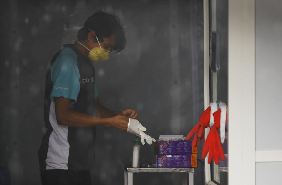 """Nhuja Kaiju, of the RNA-16 volunteer group, takes off his gloves after assisting nurses at a hospital in Bhaktapur, Nepal, Tuesday, May 26, 2020. RNA-16 stands for """"Rescue and Awareness"""" and the 16 kinds of disasters they have prepared to deal with, from Nepal's devastating 2015 earthquake to road accidents. But the unique services of this group of three men and a woman in signature blue vests in the epidemic amount to a much greater sacrifice, said doctors, hospital officials and civic leaders. (AP Photo/Niranjan Shrestha)"""