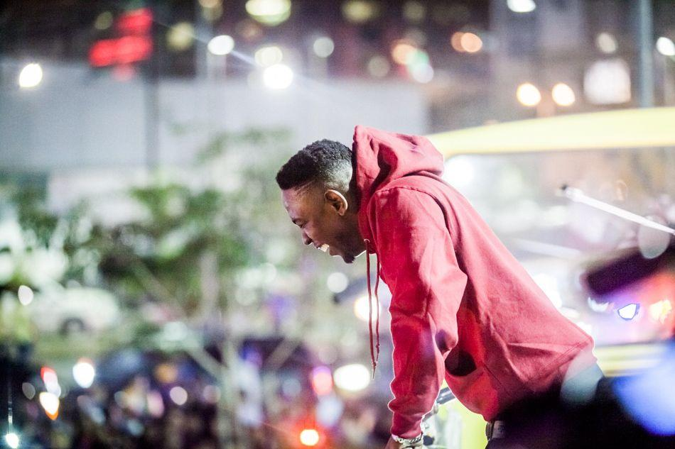 Kendrick Lamar leans over double decker bus to view the Yahoo! Crash Concerts crowd.