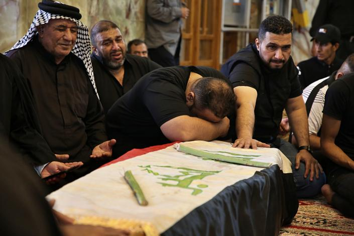 Mourners pray over the flag-draped coffin of a protester killed during anti-government protesters during his funeral at the Imam Ali shrine in Najaf, Iraq, Saturday, Oct. 5, 2019. The spontaneous protests which started Tuesday in Baghdad and southern cities were sparked by endemic corruption and lack of jobs. Security responded with a harsh crackdown, leaving more than 70 killed. (AP Photo/Anmar Khalil)