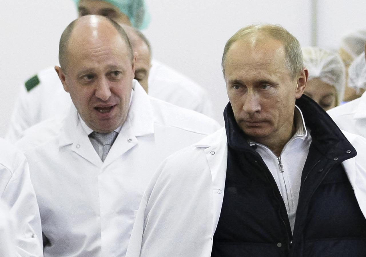 """FILE - In this Monday, Sept. 20, 2010 file photo, businessman Yevgeny Prigozhin, left, shows Russian President Vladimir Putin, around his factory which produces school means, outside St. Petersburg, Russia. One of those indicted in the Russia probe is a businessman with ties to Russian President Vladimir Putin. Prigozhin is an entrepreneur from St. Petersburg who's been dubbed """"Putin's chef"""" by Russian media. His restaurants and catering businesses have hosted the Kremlin leader's dinners with foreign dignitaries. (Alexei Druzhinin, Sputnik, Kremlin Pool Photo via AP, File)"""