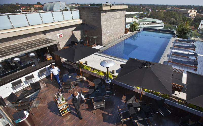 In this photo taken Wednesday, Sept. 26, 2012, a member of staff wheels drinks at the rooftop pool of the Sankara Nairobi hotel in Nairobi, Kenya. International hotel developers are planning nearly 40,000 new rooms across Africa in the coming years, the continent's business travel is increasing, and Africa's middle class will soon begin leisure travel en masse. (AP Photo/Ben Curtis)