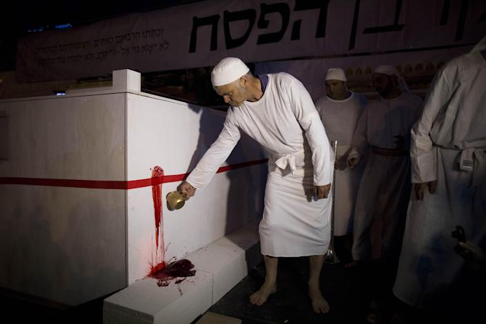 An Orthodox Jew from the Temple Mount Institute wearing the garb of cohan (priest) spills the blood of a lamb slaughtered on the altar during the reenactment of the Passover sacrifice ceremony in Jerusalem in 2014. (Photo: Abir Sultan/Epa/REX/Shutterstock)