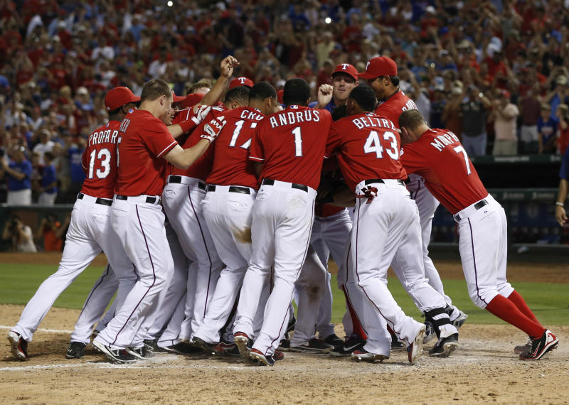 Texas Rangers' teammates swarm Geovany Soto after his walk-off home run against the Los Angeles Angels during the ninth inning of a baseball game, Monday, July 29, 2013, in Arlington, Texas. The Rangers won 4-3. (AP Photo/Jim Cowsert)