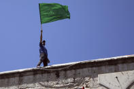 A worshipper waves the Hamas flag during a protest against the likely evictions of Palestinian families from the homes, after the last Friday prayers of the Muslim holy month of Ramadan at the Dome of the Rock Mosque in the Al Aqsa Mosque compound in the Old City of Jerusalem, Jerusalem, Friday, May 7, 2021. (AP Photo/Mahmoud Illean)