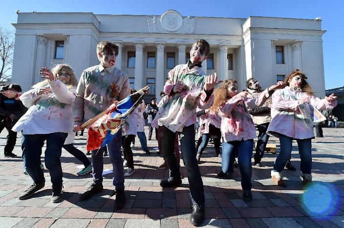 """Demonstrators dressed as zombies shout mock slogans """"We like Russian TV, we like Putin"""" during a protest in Kiev, demanding Ukrainian lawmakers banning Russian television programmes which they consider to be propaganda (AFP Photo/Sergei Supinsky)"""
