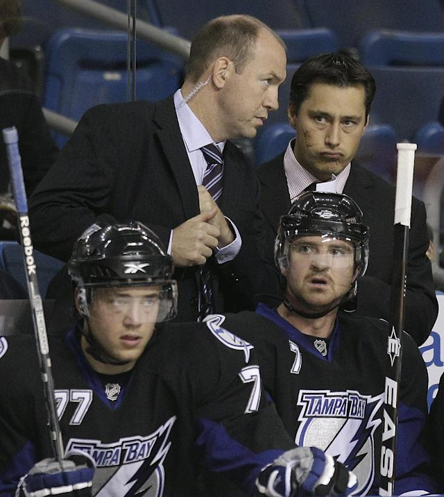 New Tampa Bay Lightning coach Guy Boucher, right, talks with assistant coach Dan Lacroix as players Victor Hedman, (77) of Finland, and Brett Clark (7) watch the NHL preseason hockey game with the Florida Panthers on Saturday, Oct. 2, 2010, in Tampa, Fla. (AP Photo/Chris O'Meara)