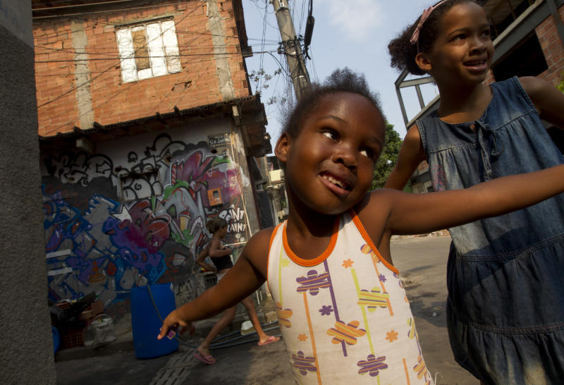 In this Dec. 28, 2012 photo, children play in the Mare shantytown, in Rio de Janeiro, Brazil. The city's densest neighborhoods, its favelas, or shantytowns blanket entire hillsides, providing most of the city's affordable housing. Now, those communities are being charted after decades of informality, each route and alley outlined and their names researched. A nonprofit organization run by current and former favela residents called Redes da Mare kick-started the first mapping program in the grouping of favelas known as Mare with a simple but powerful goal: putting their homes on the map, with named streets, zip codes and official addresses. (AP Photo/Silvia Izquierdo)