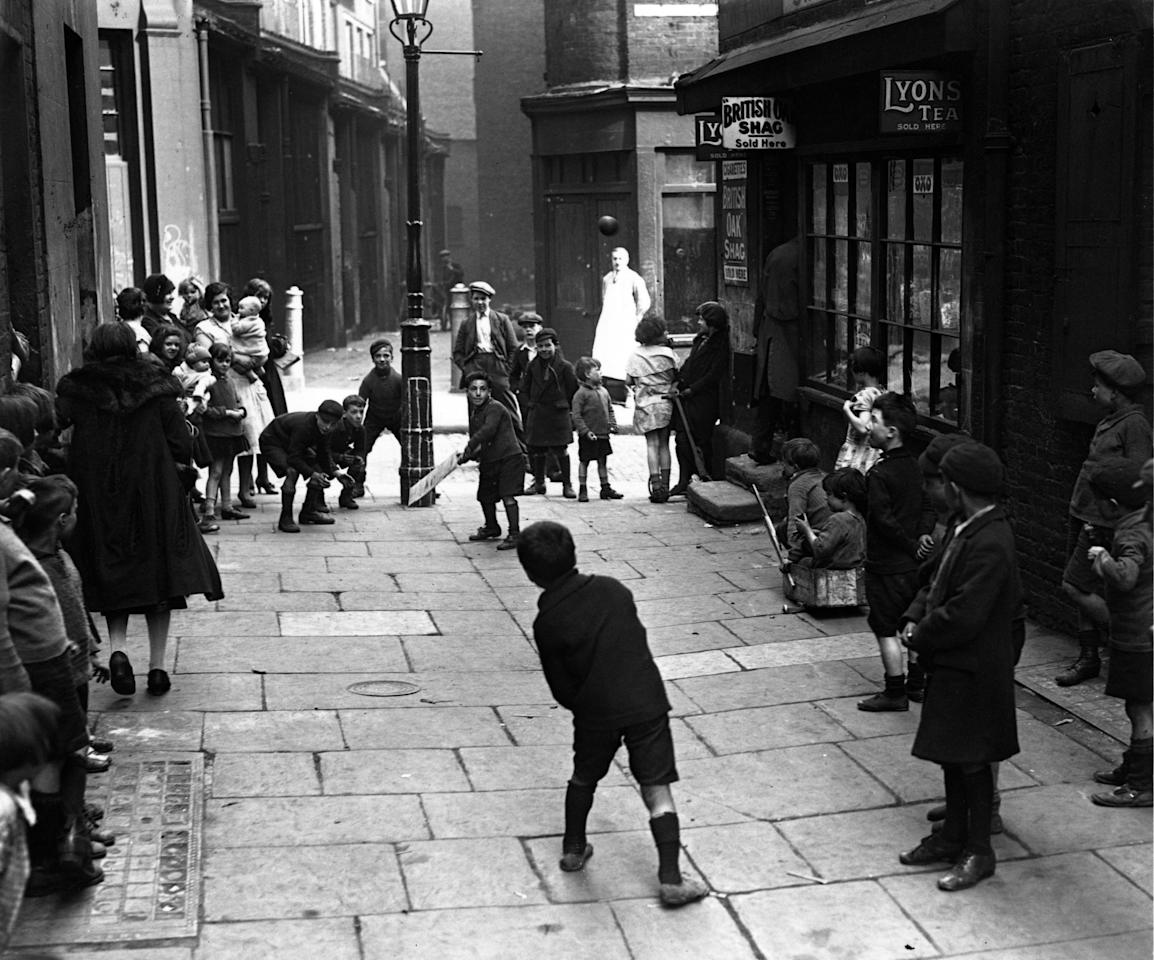25th April 1930:  Children playing cricket in a London street, with the wicket drawn on a lamppost.  (Photo by Fox Photos/Getty Images)
