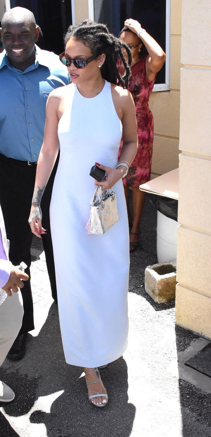 <p>BadGal RiRi dresses up in a white with a racer-front dress, metallic handbag, grey strappy sandals and retro-looking sunglasses at a church in Barbados for her cousin's christening.</p>