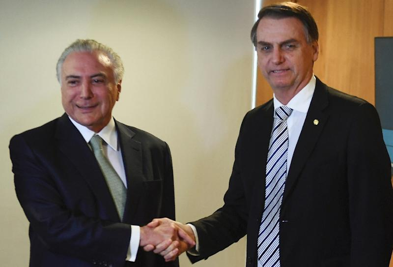 Outgoing Brazilian President Michel Temer (L) shakes hands with President-elect Jair Bolsonaro -- it was the pair's first meeting since Bolsonaro's election win