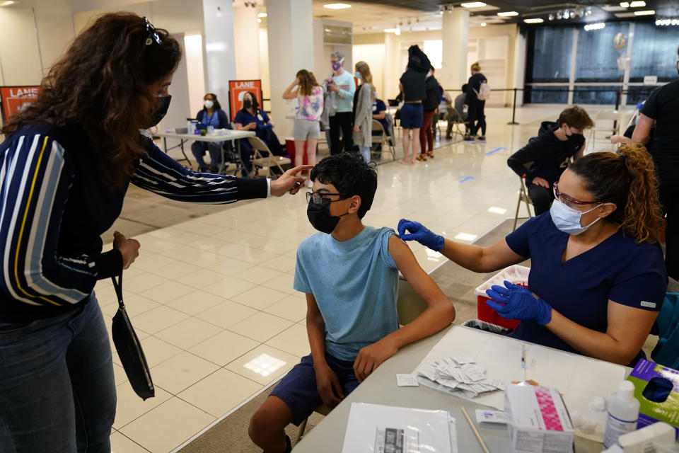 Nouf Albarakati, left, of Narberth Pa., comforts her son Manaf Albarakati, 14, before he receives a Pfizer COVID-19 vaccination from registered nurse Alicia Jimenez at a Montgomery County, Pa. Office of Public Health vaccination clinic at the King of Prussia Mall, Tuesday, May 11, 2021, in King of Prussia, Pa. (AP Photo/Matt Slocum)