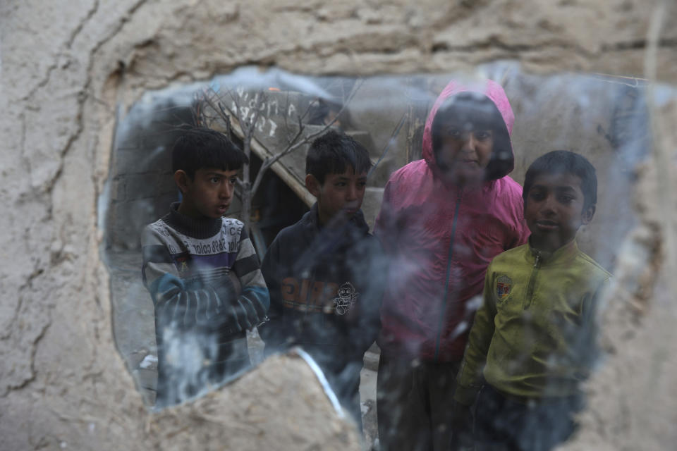 Internally displaced boys are reflected in a mirror inside their temporary home in the city of Kabul, Afghanistan, Wednesday, Dec. 30, 2020. Save the Children has warned that more than 300,000 Afghan children face freezing winter conditions that could lead to illness, in the worst cases death, without proper winter clothing and heating. (AP Photo/Rahmat Gul)