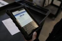 Nabis warehouse associate David Garcia holds a tablet with cannabis orders that he uses to pick products from the shelves at the Nabis warehouse in Oakland