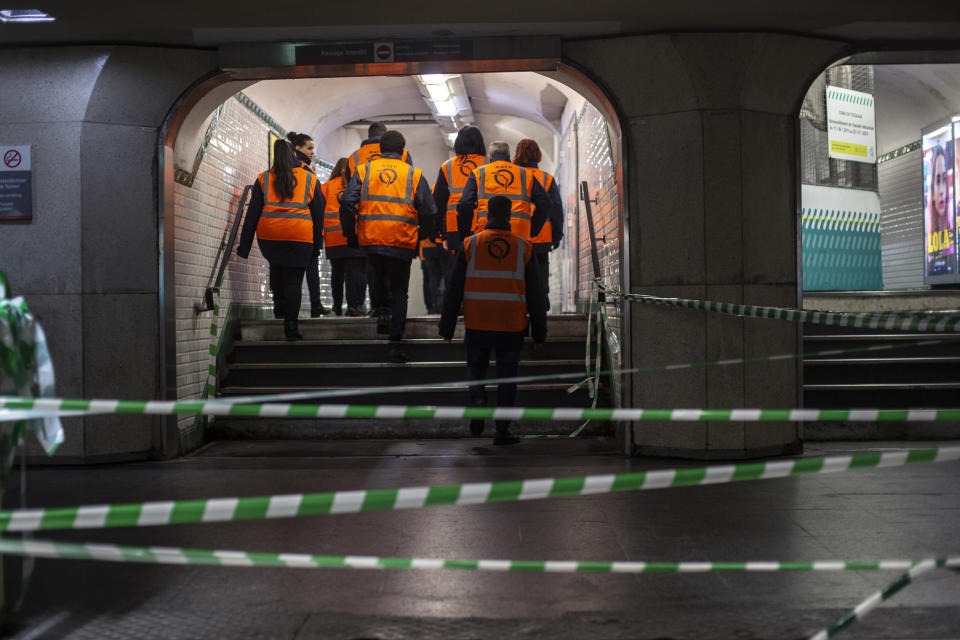 """Paris subway employees walk in a corridor of a subway station in Paris, Monday, Dec.9, 2019. Paris commuters inched to work Monday through exceptional traffic jams, as strikes to preserve retirement rights halted trains and subways for a fifth straight day. Citing safety risks, the SNCF national rail network issued warned travelers to stay home or use """"alternate means of locomotion"""" to get to work Monday instead of thronging platforms in hopes of getting the few available trains. (AP Photo/Rafael Yaghobzadeh)"""