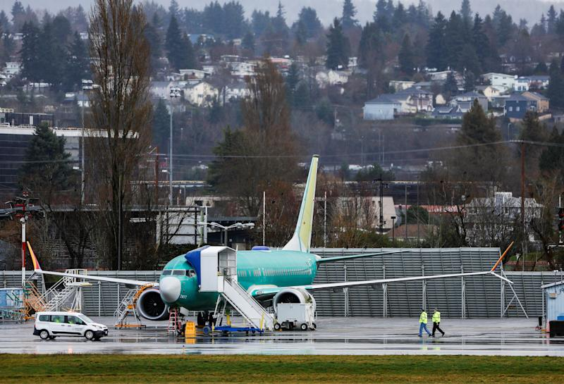 Employees walk near a Boeing 737 Max aircraft at the Renton Municipal Airport in Renton, Washington, U.S. January 10, 2020. REUTERS/Lindsey Wasson