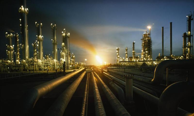 Gas fires light the night sky at the heavily lit Ras Tanurah oil refinery in Saudi Arabia