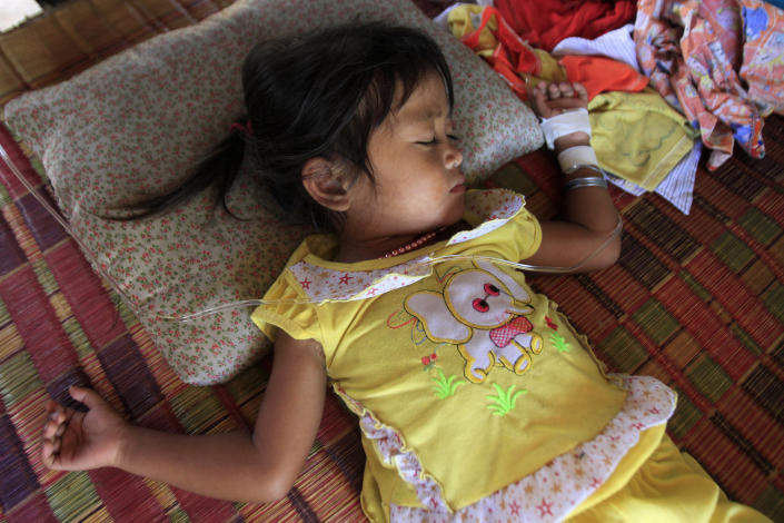 FILE- In this Monday, July 9, 2012, file photo, Mean Thida, 4, affected with mystery disease, sleeps at her home near a dump site at Sambour village, on the outskirts of Phnom Penh, Cambodia. The enterovirus 71 strain, or EV-71, raised fears earlier this week after it was detected in some lab samples taken after 52 of 59 Cambodian children died suddenly from a mystery illness that sparked international alarm. Health officials are still investigating, but say the virus is likely to blame. (AP Photo/Heng Sinith, File)