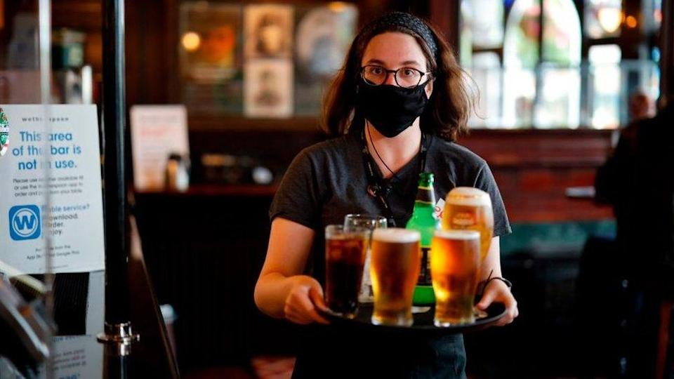 Pub worker serving drinks wearing a face covering