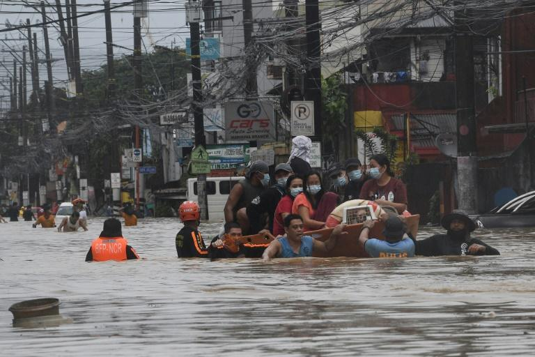Rescuers evacuate residents from their flooded homes in Manila