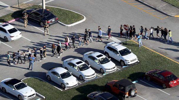 PHOTO: People are brought out of the Marjory Stoneman Douglas High School after a shooting, Feb. 14, 2018, in Parkland, Florida. (Joe Raedle/Getty Images)