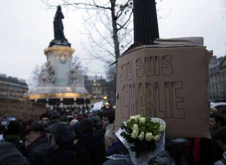 """A bouquet of roses is seen near a placard which reads """"I am Charlie"""" displayed to pay tribute during a gathering at the Place de la Republique in Paris January 7, 2015, following a shooting by gunmen at the offices of weekly satirical magazine Charlie Hebdo. REUTERS/Gonzalo Fuentes"""