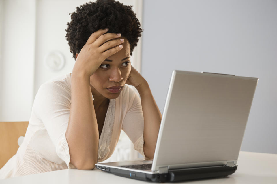 Frustrated Black businesswoman using laptop