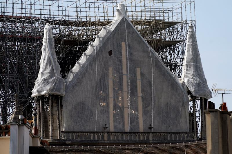 Work began draping protective covers over Notre-Dame on Monday, with climbers expected to install protective tarpaulins on Tuesday ahead of the rains