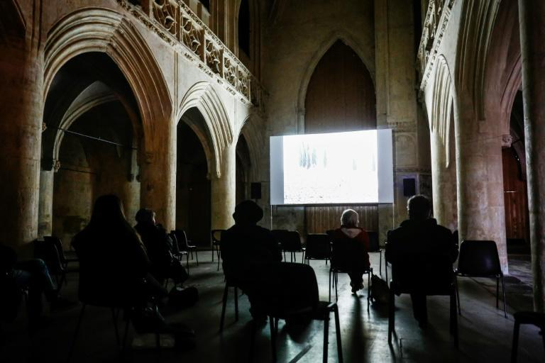 People watch a film while socially distancing at the Vieux Saint-Sauveur church in Caen, northern France