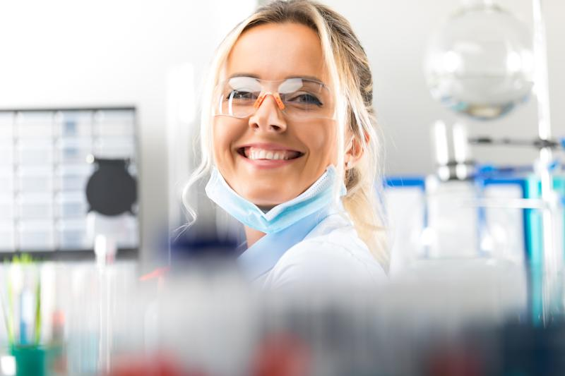 A female scientist smiling in a lab.