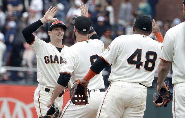 San Francisco Giants left fielder Mike Yastrzemski, left, celebrates with first baseman Brandon Belt, center, and third baseman Pablo Sandoval (48) after they defeated the Milwaukee Brewers in a baseball game in San Francisco, Saturday, June 15, 2019. (AP Photo/Jeff Chiu)