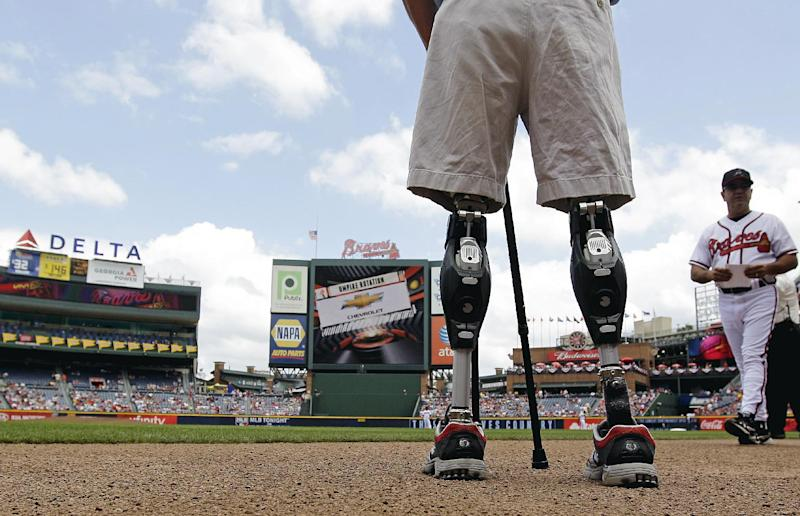 FILE - In this Monday, May 28, 2012 file photo, U.S. Army Capt. Dan Berschinski, foreground, uses prosthetic legs to stand on the field before a baseball game between the St. Louis Cardinals and Atlanta Braves in Atlanta. Berschinski lost both legs to an IED blast while serving in Afghanistan in 2009. Nearly 2,000 American troops have lost a leg, arm, foot or hand in Iraq or Afghanistan, and their sacrifices have led to advances in the immediate and long-term care of survivors, as well in the quality of prosthetics that are now so good that surgeons often chose them over trying to save a badly mangled leg.  (AP Photo/David Goldman)