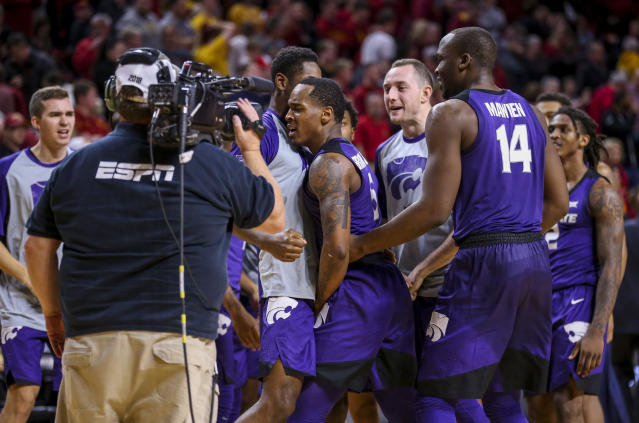 Kansas State guard Barry Brown Jr. is mobbed by his teammates after their 58-57 victory over Iowa State during an NCAA college basketball game, Saturday, Jan. 12, 2019, in Ames, Iowa. Barry Brown Jr. made a layup with less than 5 seconds remaining to give Kansas State the lead and win. (AP Photo/Justin Hayworth)