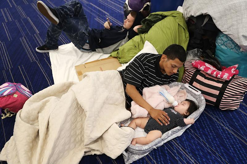 Mark Ocosta and his baby, Aubrey Ocosta, take shelter at the George R. Brown Convention Center after floodwaters inundatedHouston on Aug. 29, 2017. (Joe Raedle via Getty Images)