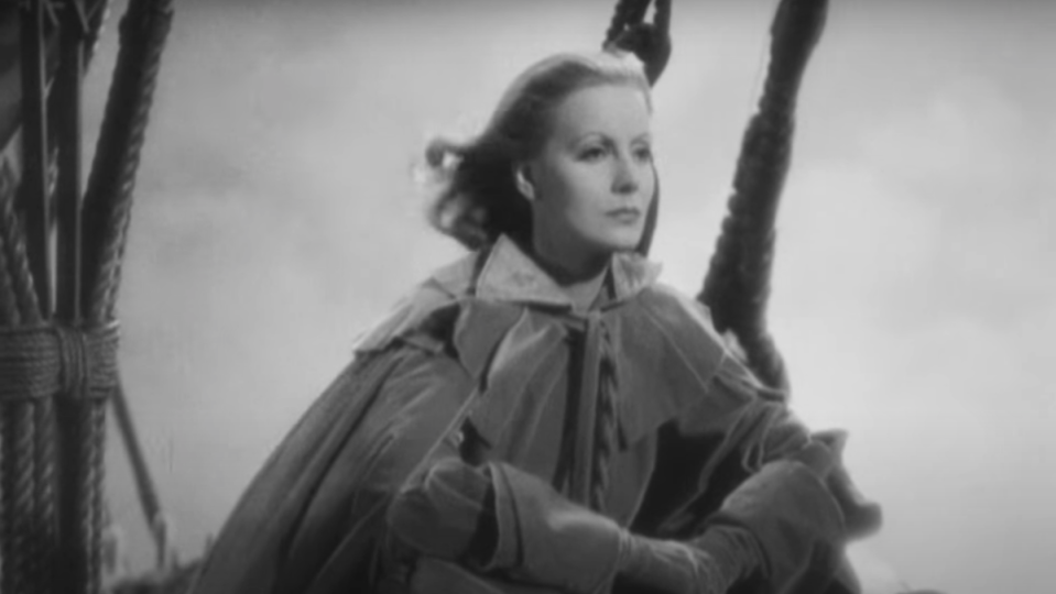 Greta Garbo looks over the bow of a sailboat