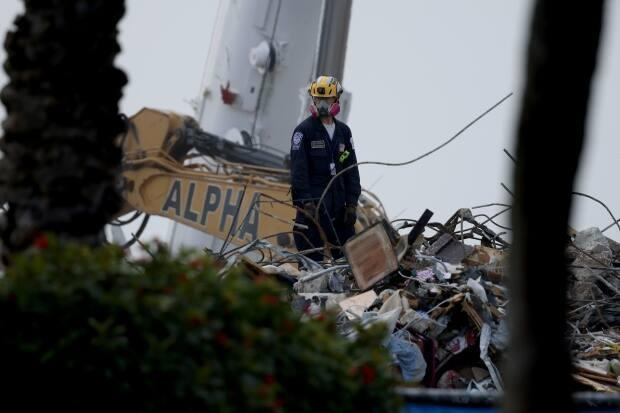 A rescue worker is seen at the site of a collapsed condo building in Surfside, Fla., on Saturday. (Anna Moneymaker/Getty Images - image credit)