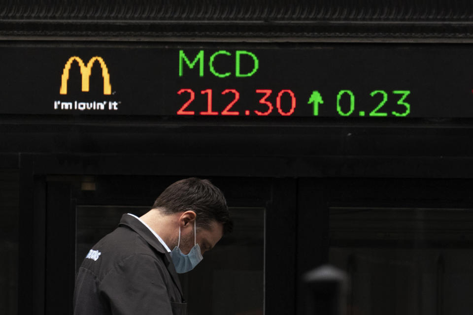 A man walks by a stock ticker displaying the cost of McDonald's shares at the New York Stock Exchange, Tuesday, Feb. 23, 2021. On Wednesday, April 28, President Joe Biden is expected to propose doubling the tax rate that the highest-earning Americans pay on profits made from stocks and other investments. (AP Photo/Mark Lennihan)
